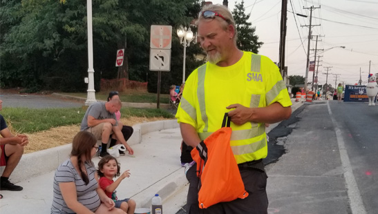 At the Hampstead Volunteer Fire Department Carnival parade, FMIT III John Buschelberger of the Westminster Shop distributed safety bracelets and candy to children and adults along a road being repaired by MDOT SHA.
