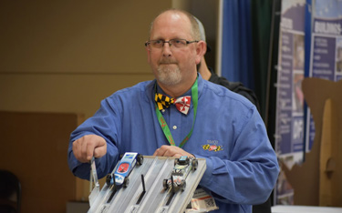 At MdQI, OPPE Assistant Division Chief Dennis Atkins checked out two competitors in the annual Pinewood Derby.