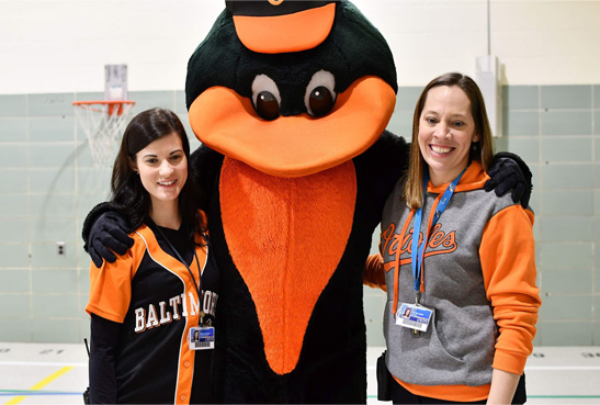 Assistant Principal Donna M. Buppert (left) and Principal Rachel J. Davis welcomed the Orioles Bird to an MDOT SHA pedestrian safety program at Grange Elementary School in Baltimore on Feb. 14.