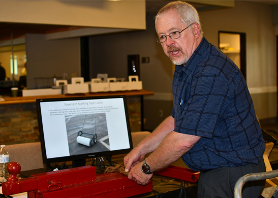 D6 RME Rick Cosner demonstrates one of his shop's inventions, a tailgate latch extender, while a second creation, a pavement marking caddy, appears onscreen. The caddy earned Cosner a field operations award.